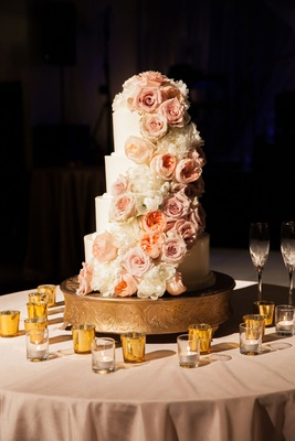 a four-tier white wedding cake with cascading ivory and blush flowers
