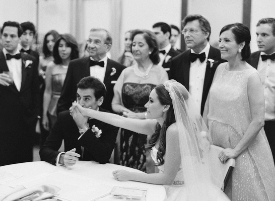 Black and white photo of groom kissing bride's hand at ketubah signing ceremony before wedding