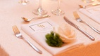 calligraphy place card escort card on white napkin on white table linen with white rose greenery