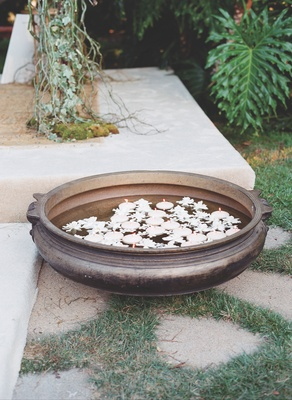 Outdoor wedding with Indian uruli bowls containing floating candles and flowers