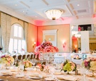 Ballroom reception crystal candelabra topped with pink roses and lower arrangements on long tables