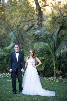 Bride in strapless Mira Zwillinger wedding dress hair in curls and red flowers, groom in tuxedo