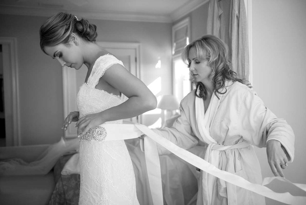 Black and white photo of bridesmaid tying wedding belt