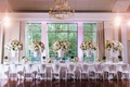 Head table with white chairs, white linen, lucite risers, white ginger jar centerpieces, flowers