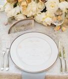 Place setting with gold calligraphy agate slice geode white rose and gold leaf centerpiece