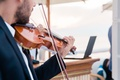 close-up of violin being played during outdoor weddin