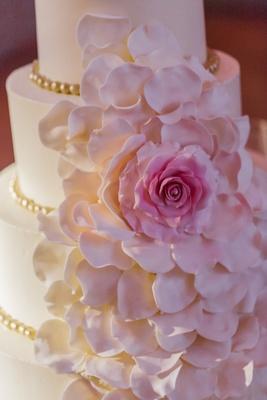 Cake adorned with cascading pink sugar flower