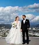 bride in marchesa long sleeve wedding dress and groom in tuxedo long hair portrait helipad rooftop