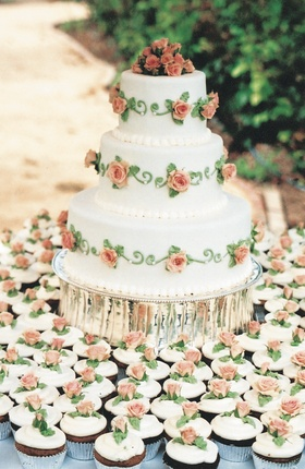 Three layer cake with roses and matching cupcakes