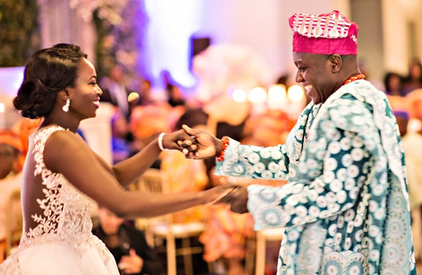 Bride in illusion back wedding dress dances with father of bride in traditional Nigerian attire