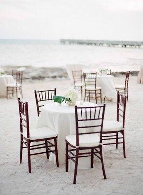 Beach wedding cocktail hour on sand in Key West with wood chairs white tablecloth linens