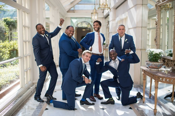 a groom and his groomsmen playfully pose in blue suits with varying ties before ceremony