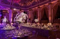 Opulent ballroom reception with white orchids and clear tables