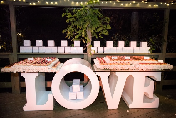 gourmet donut wedding favors on table that spells out love