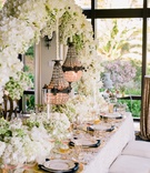 Wedding reception table with white floral arch and suspended glass beaded chandeliers