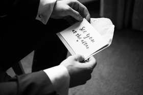 black and white photo of groom holding note from bride before the ceremony