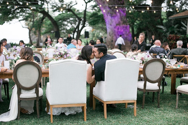 bride and groom in armchairs at head table outdoor reception hawaii kiss newlyweds