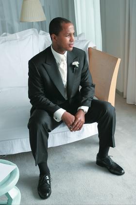 Groom sitting on chaise preparing for wedding