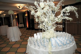 Round table covered in white tablecloth with tree
