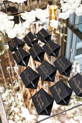 Black escort cards on glass mirror table with gold calligraphy