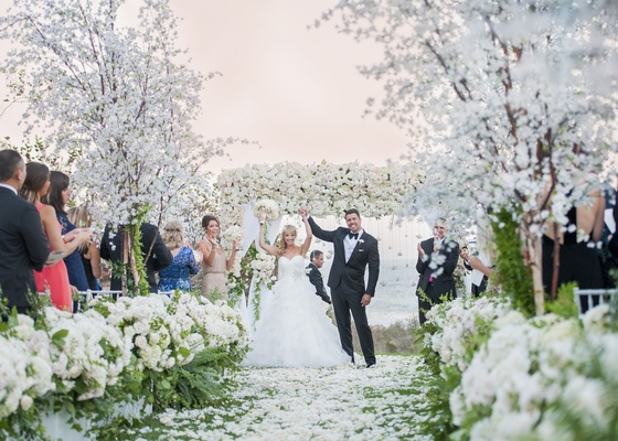 bride in full ruffled ball gown, groom in tuxedo, raise arms in celebration after being married