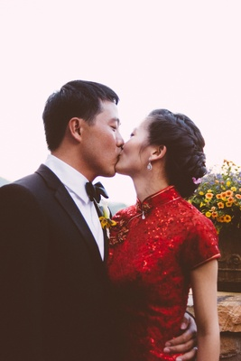 Chinese man kissing woman in traditonal red dress