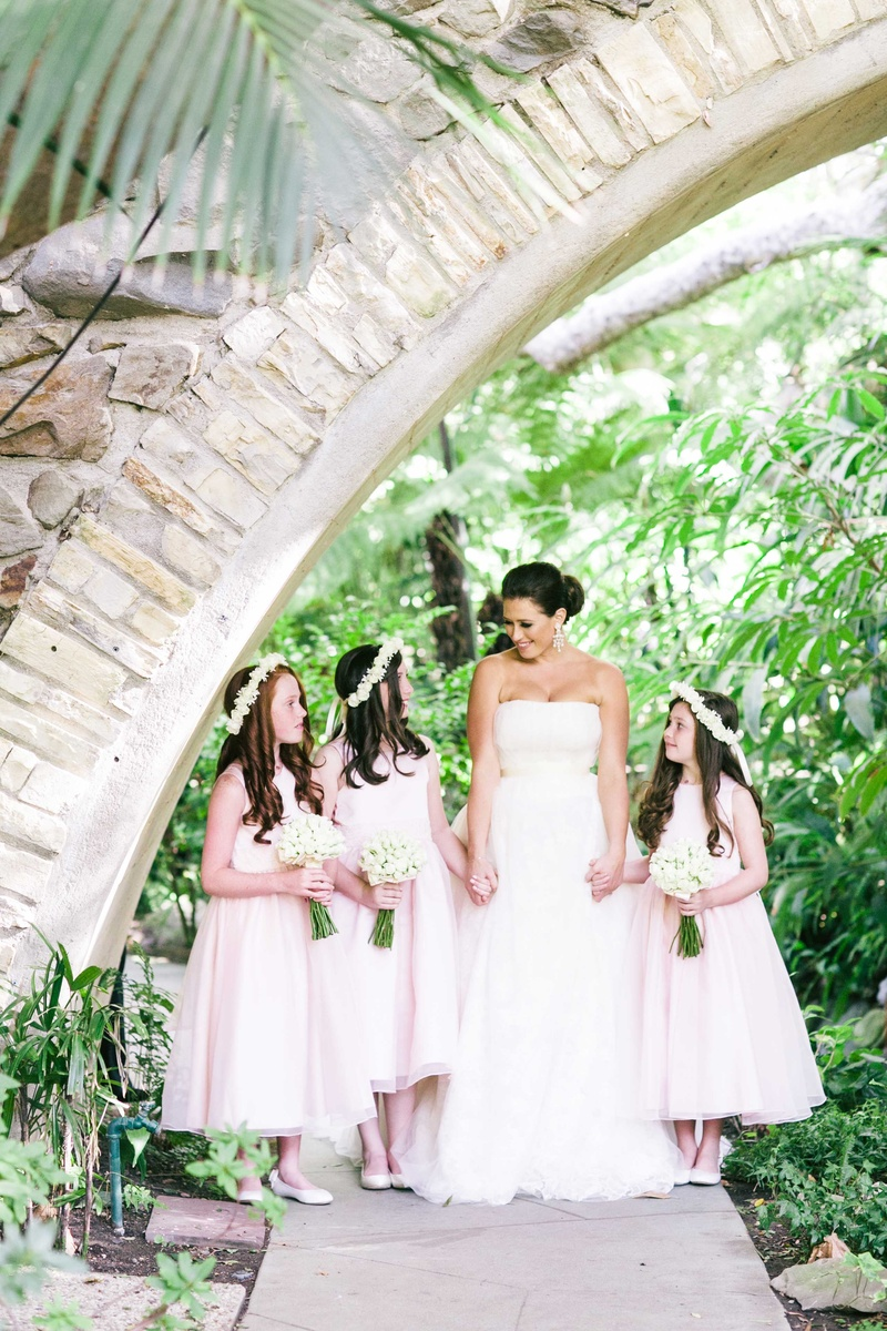 Bride holding hands with flower girls in light pink tea length dresses with white flower crowns