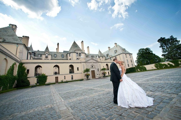 Bride in a strapless Pnina Tornai ball gown kisses groom in a black tuxedo at Oheka Castle