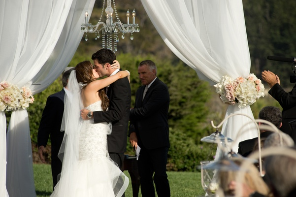 Newlyweds kiss under white chuppah and chandelier