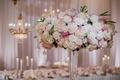 Tall wedding reception arrangement of blush, white hydrangeas, roses