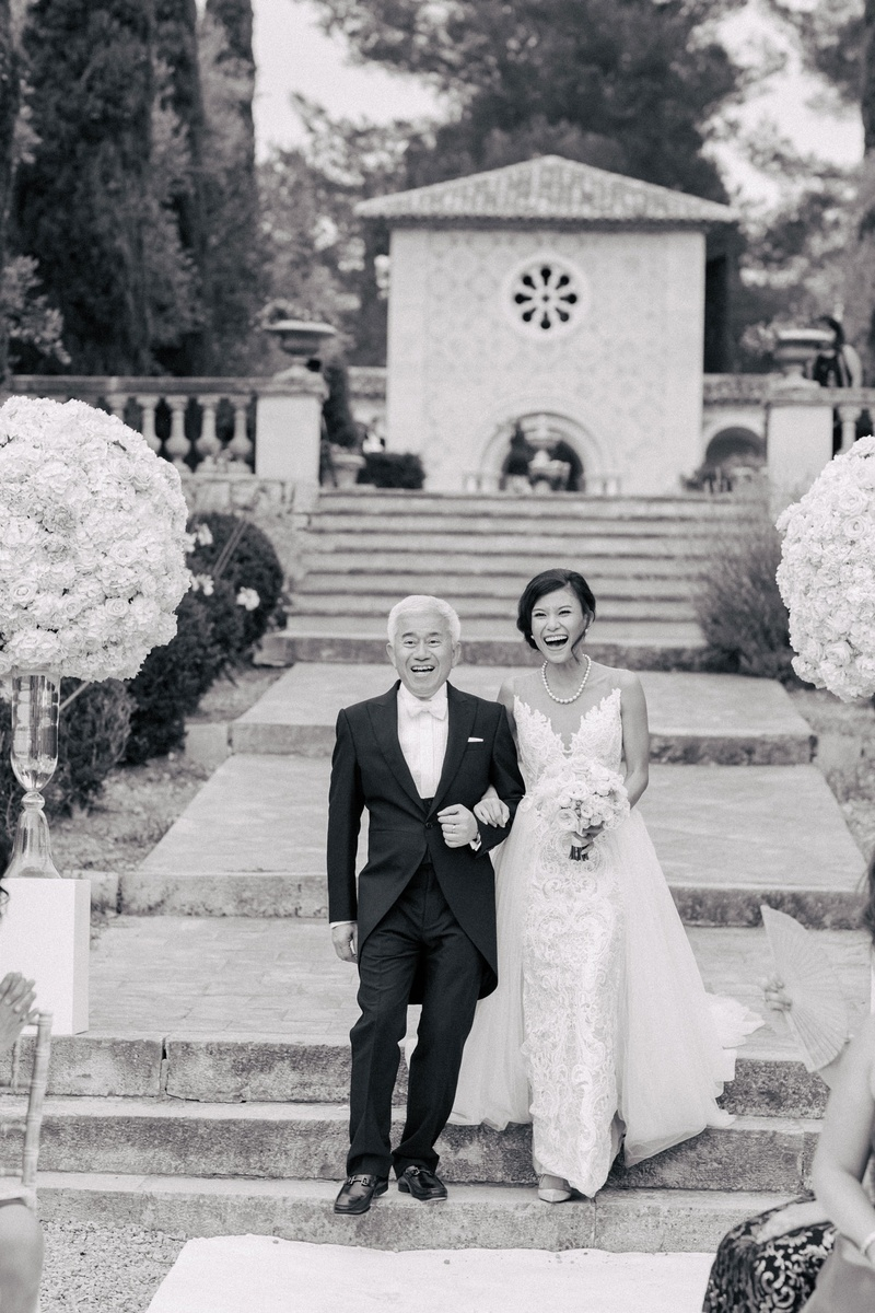 Black and white photo of bride and father of bride walking toward aisle outdoor venue in France