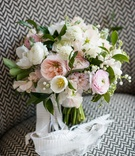 Bride's bouquet with pink ranunculus, tulips, peonies, garden roses and verdure, lily of the valley