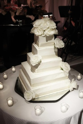 White cake with ribbons and roses