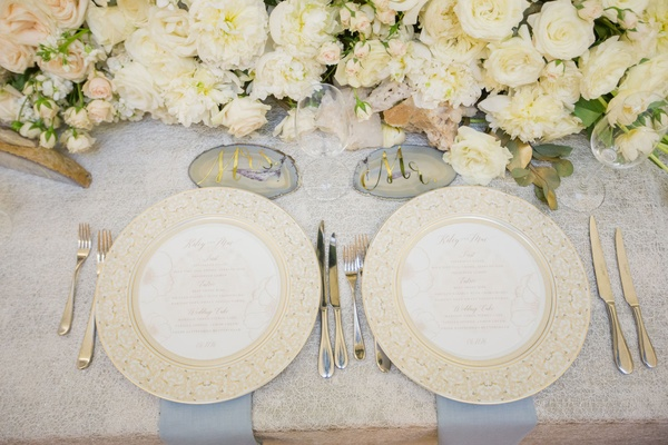 ivory centerpiece with crystals, agate slices with gold foil calligraphy white flowers roses