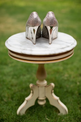 Shiny metallic Jimmy Choo wedges on marble table