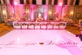 White dance floor with couples names and heart in front of head table and cake pink lighting