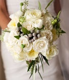 White rose, white garden rose, greenery, winter berries in fall winter bridal bouquet