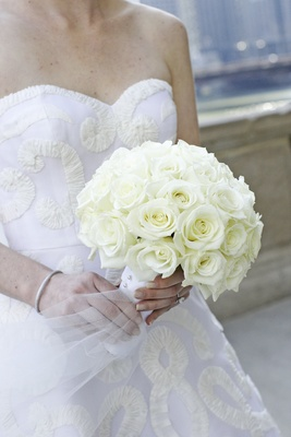 Bride holds bouquet of only white roses