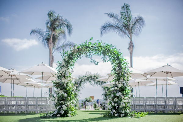 wedding ceremony greenery arch white flowers grass lawn white chairs umbrellas shade palm trees