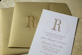 White wedding invitation stamped with the letter R and wavy design, gilt envelopes