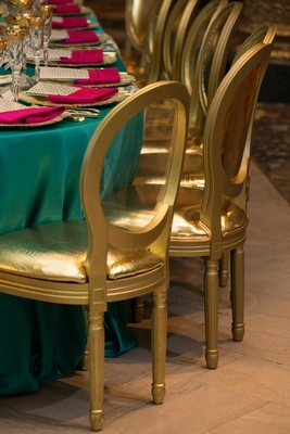 gold shiny cushioned chairs at bold blue linens with bright pink napkins