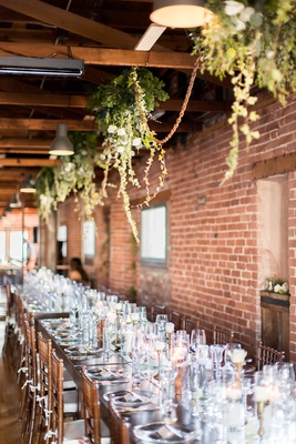 Brick wall wedding reception decor suspended greenery arrangements wood table chairs white cushions