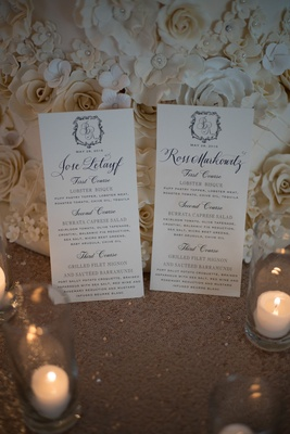 Calligraphy menus with names of each guest and monogram in front of wedding cake