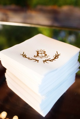 Stack of white cocktail napkins with gold wedding monogram and antler design