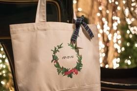 White tote bag with wedding date and holly wreath decoration tied with plaid ribbon