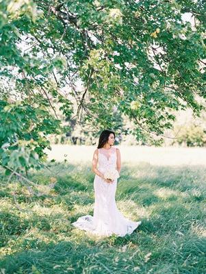 bride in sleeveless wedding dress illusion bodice plunging neckline beading lace details