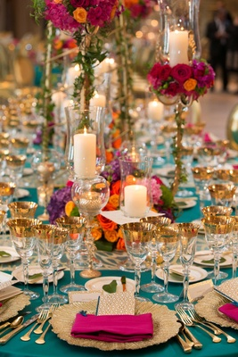turquoise linens gold flatware candles in glass vases pink napkin multi-colored arrangements