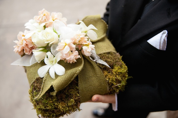 Ring bearer holds moss ring pillow with green burlap and white pink flowers