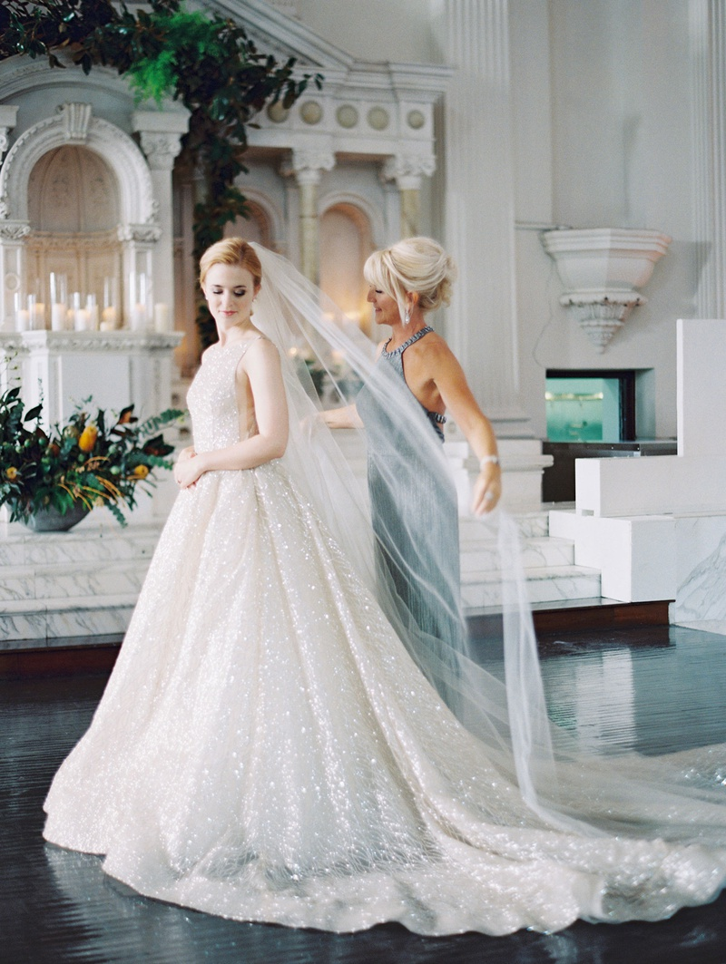 bride in sparkling lazaro wedding dress updo long veil with help from mother of bride sleeveless
