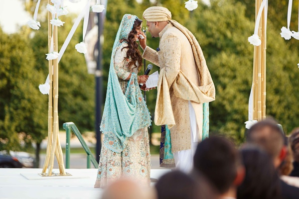 pakistani couple in traditional garb of white blue and gold exchanging vows in front of guests